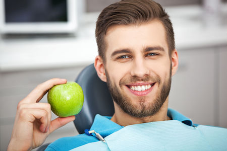 61395463 - my smile is perfect! portrait of happy patient in dental chair with green apple.